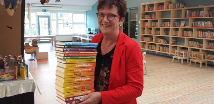 Juf Ada doneert een stapel boeken voor de schoolbibliotheek.jpg